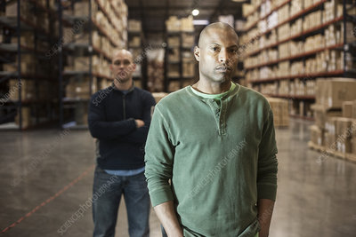 Portrait of workers in warehouse with racks of products