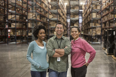 Portrait of three workers in warehouse with products in back
