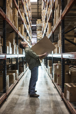 Worker in aisle, holding a box and checking inventory
