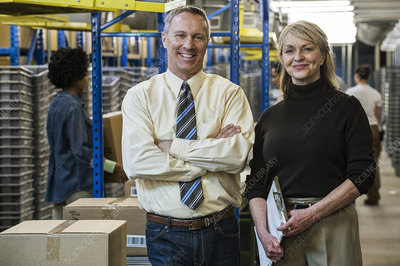 Portrait of two executives next to motorized conveyor system