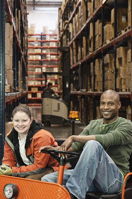 Portrait of two workers on a motorized cart in warehouse