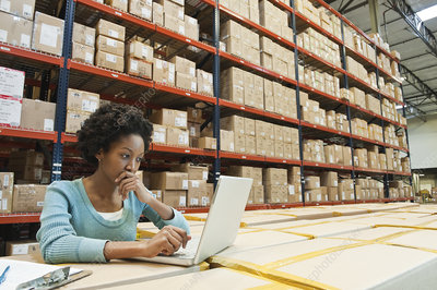 Worker doing inventory on laptop in warehouse of products