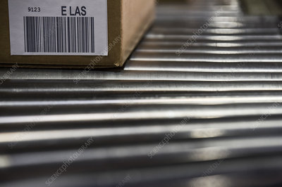 Shipping labels with bar codes on boxes on conveyor system