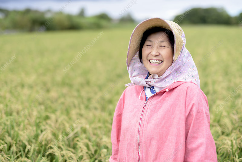 Woman wearing straw hat and pink jacket, looking at camera