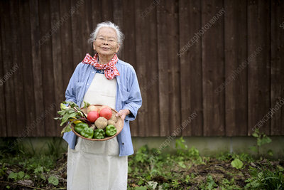 Woman holding a basket with fresh vegetables, smiling