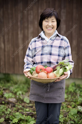 Woman in garden, holding basket of fresh vegetables, smiling