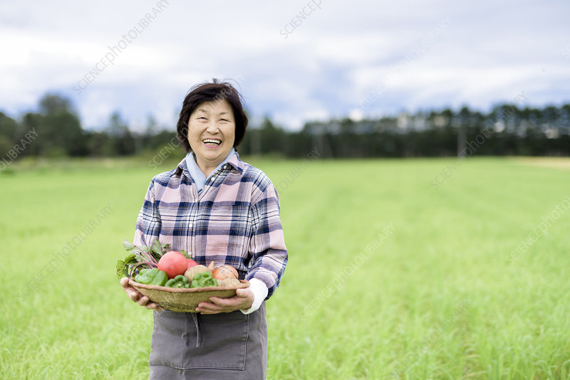 Woman in field, holding basket of fresh vegetables, smiling