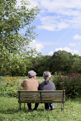 Husband and wife sitting side by side on a bench in a garden