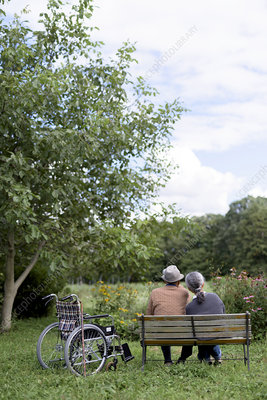 Husband and wife sitting on bench in garden with wheelchair