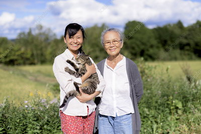 Woman holding grey cat, with an elderly woman, smiling