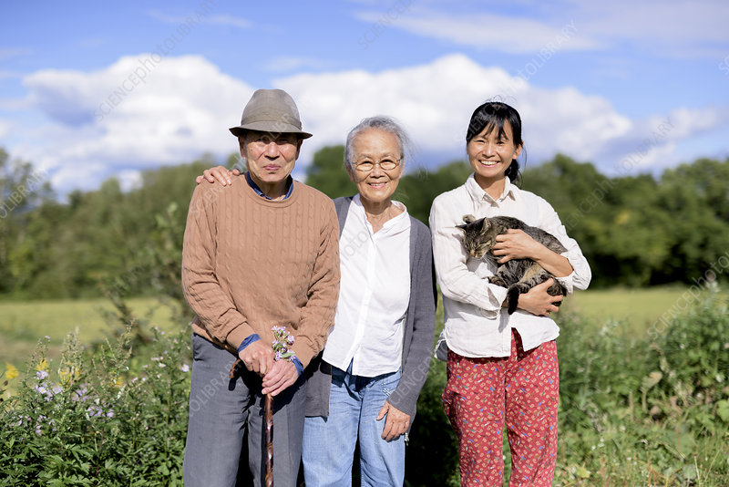 Woman holding grey cat, with an elderly couple, smiling