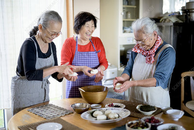 Three older women standing in a kitchen, making sushi