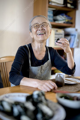 Elderly woman sitting at kitchen table, eating sushi