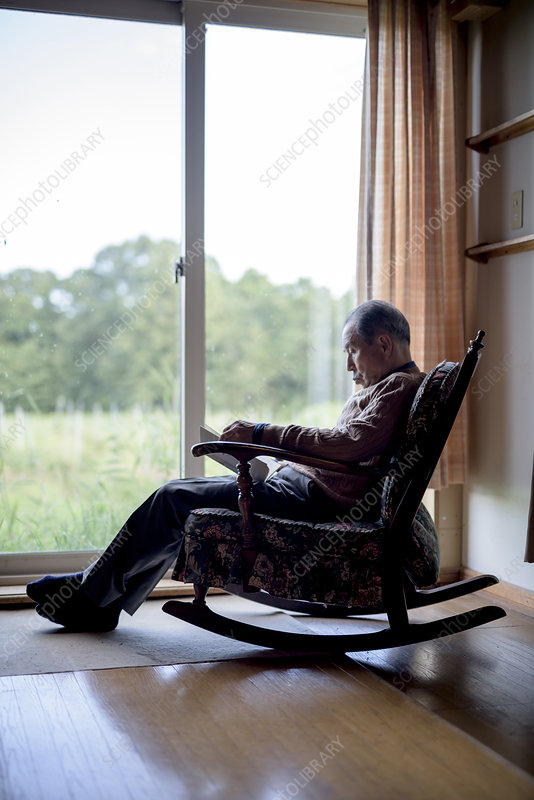 Man sitting in rocking chair by a window, reading book