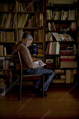 Man sitting on chair in front of bookcase, reading book