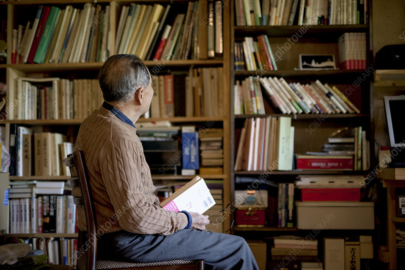 Man sitting on chair in front of bookcase, holding book