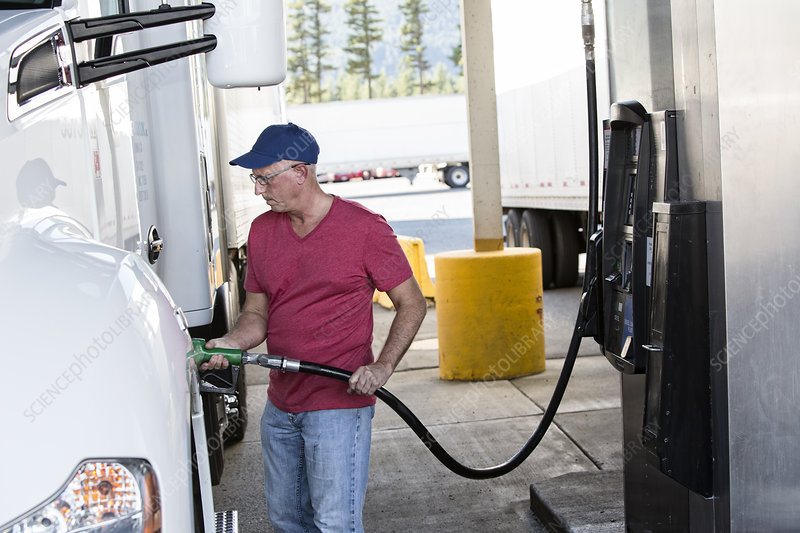 Driver putting diesel fuel in his truck at a truck stop