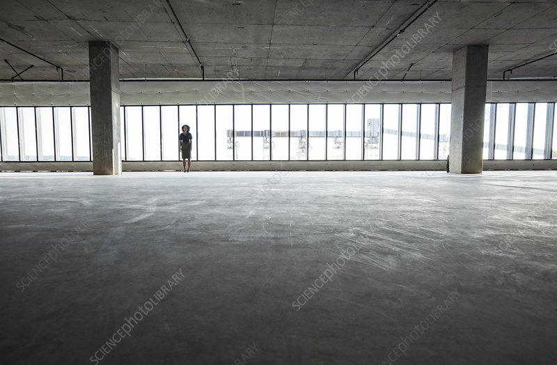 Business woman standing in a new empty raw office space