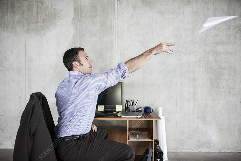 Man throwing paper airplane while at desk in office space