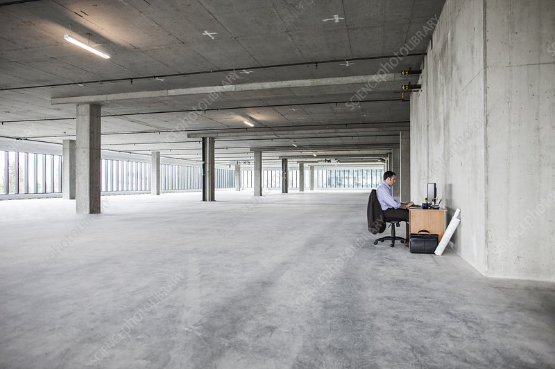 Businessman sitting at a small desk in empty office space