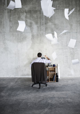 Man throwing papers in air while at desk in large raw space
