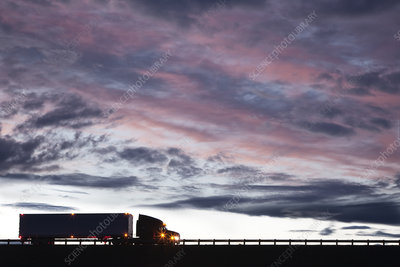 A commercial truck driving on a highway at sunset