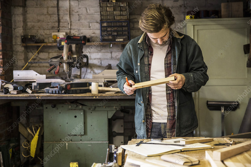 Man in a woodworking workshop, holding piece of wood