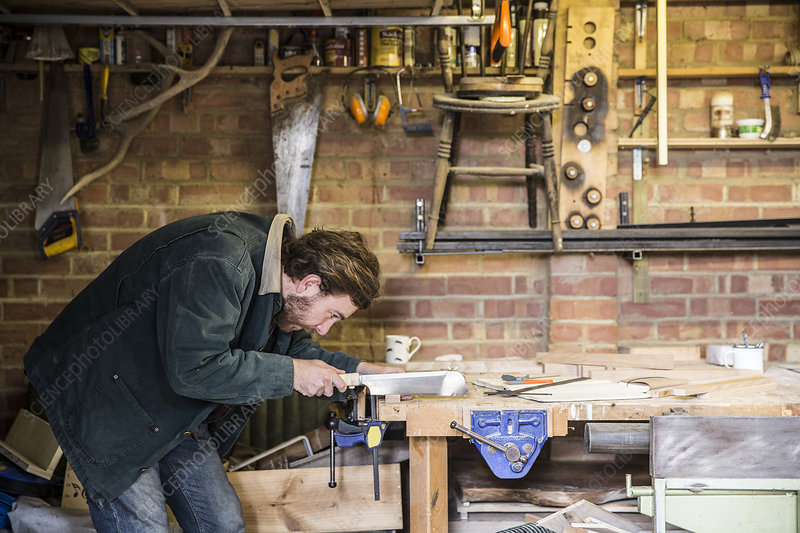 Man in a woodworking workshop, using saw on piece of wood
