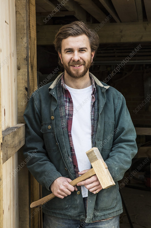 Man in woodworking workshop, holding wooden mallet, smiling