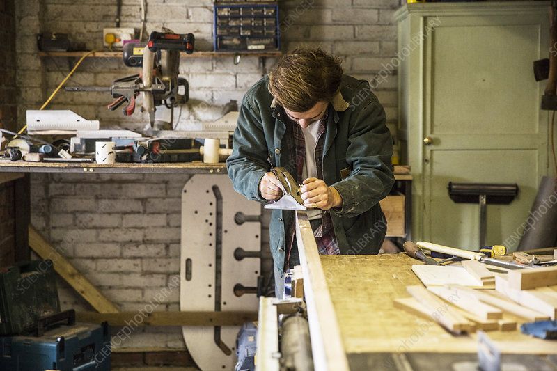 Man in woodworking workshop, using plane on plank of wood