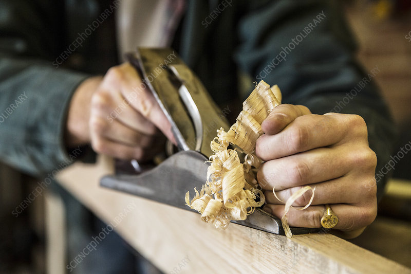 Man in a woodworking workshop, using plane on plank of wood
