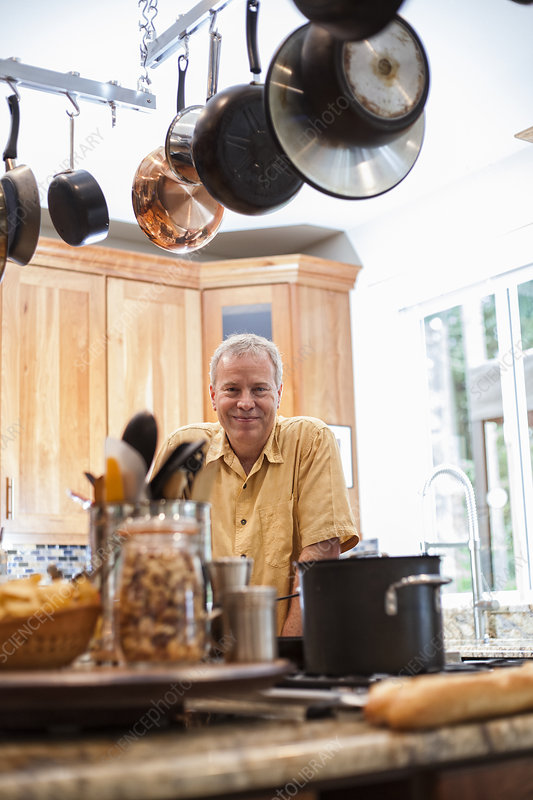 Senior man working in a home kitchen, preparing food