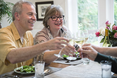 Couples toasting a dinner party with glasses of white wine