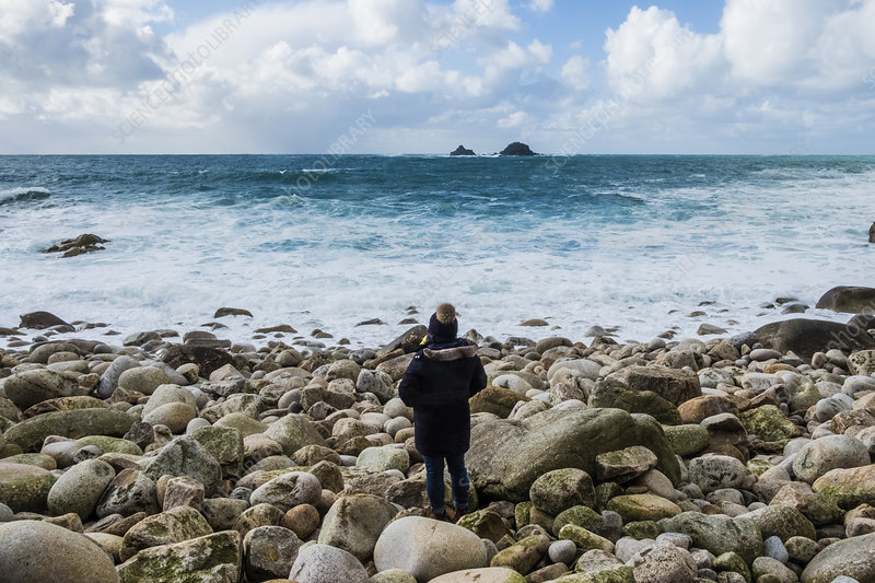 Woman looking over the Cornish coastline, and breaking waves