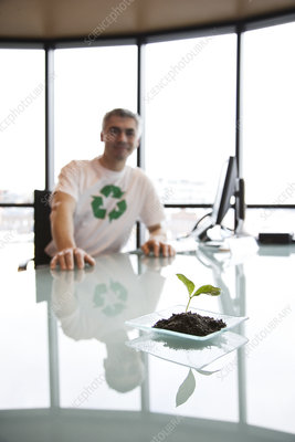 Man wearing a recycle t shirt, sitting at office desk
