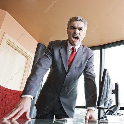 Angry businessman yelling at the viewer of the photograph