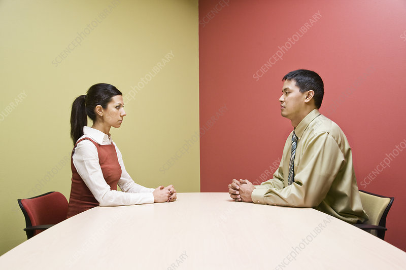 Man and woman sitting on opposite sides of conference table