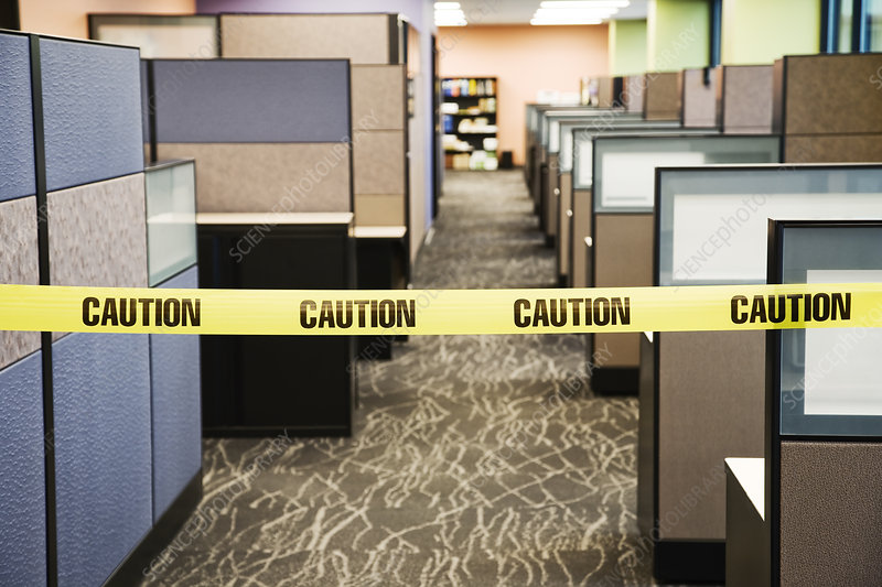 Yellow caution tape between cubicles in an office space