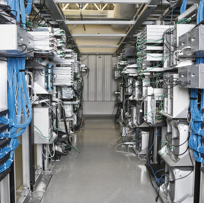 Server room aisle showing computer servers and CAT 5 cables