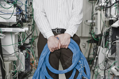 Technician holding CAT 5 cables in a computer server farm