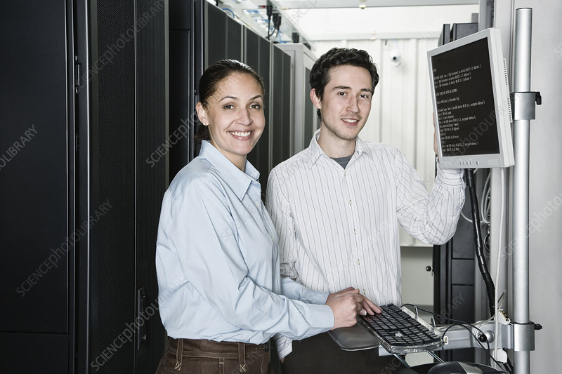 Technicians checking data on servers in computer server farm