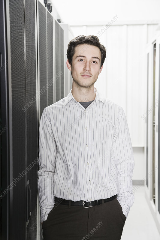Technician in aisle of servers in a computer server farm