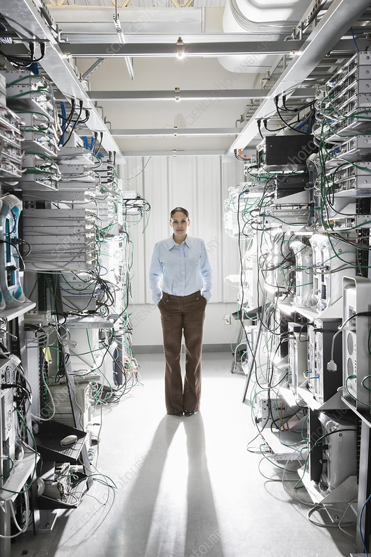 Technician working in the aisle of a computer server farm