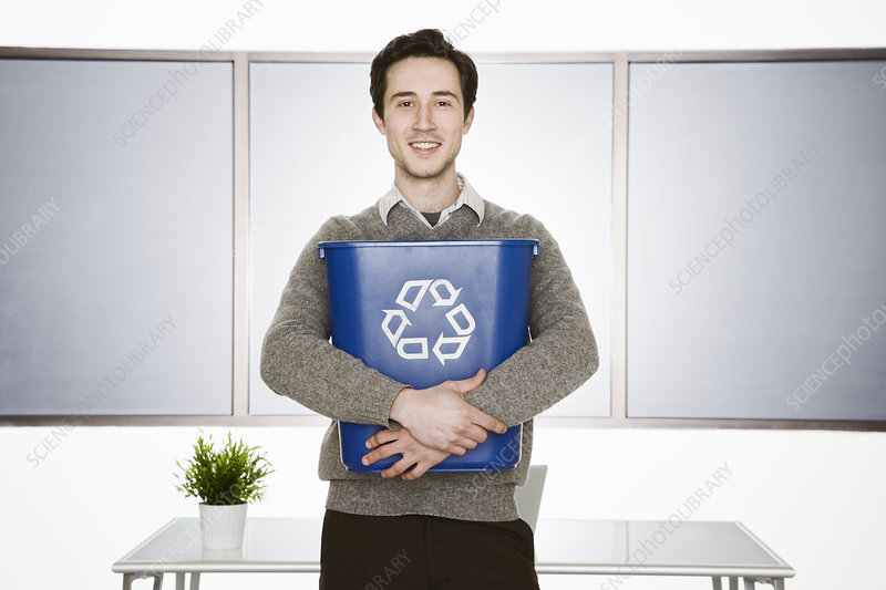 Businessman holding a recycle waste basket in his office