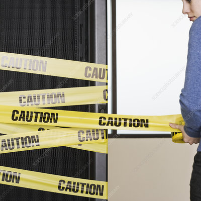Computer server rack being wrapped with yellow caution tape