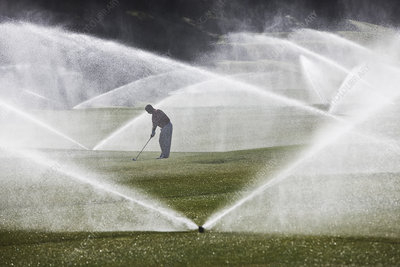 Golfer hitting his second shot on the fairway with sprinkler