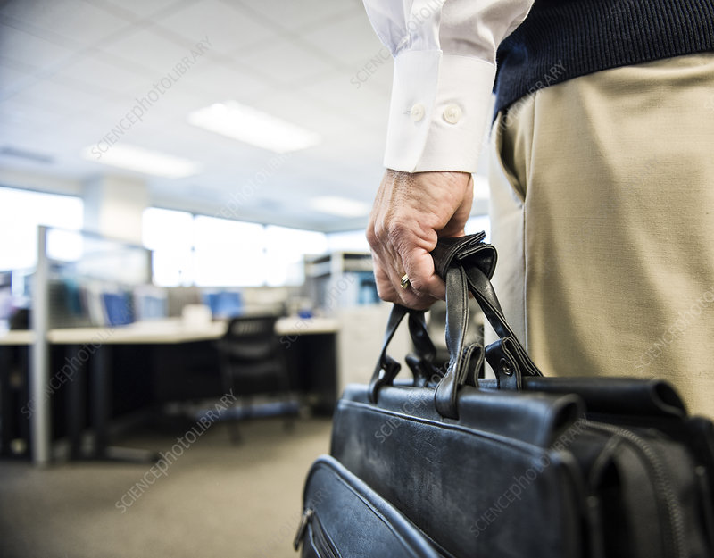 A hand carrying a brief case in an office environment