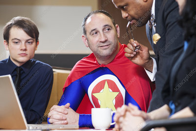 Office superhero in a meeting with his staff