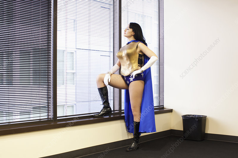 Office superhero stands at a window pondering her next move