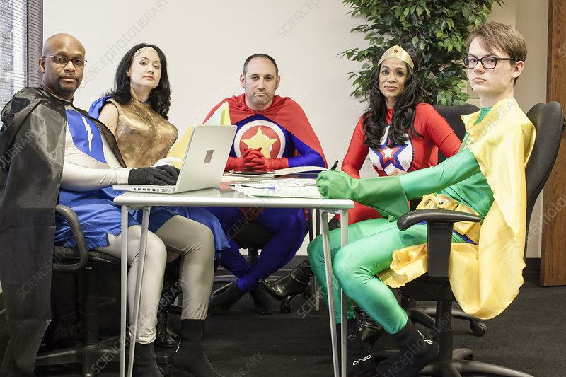 Office superheroes sitting at a table in a planning meeting